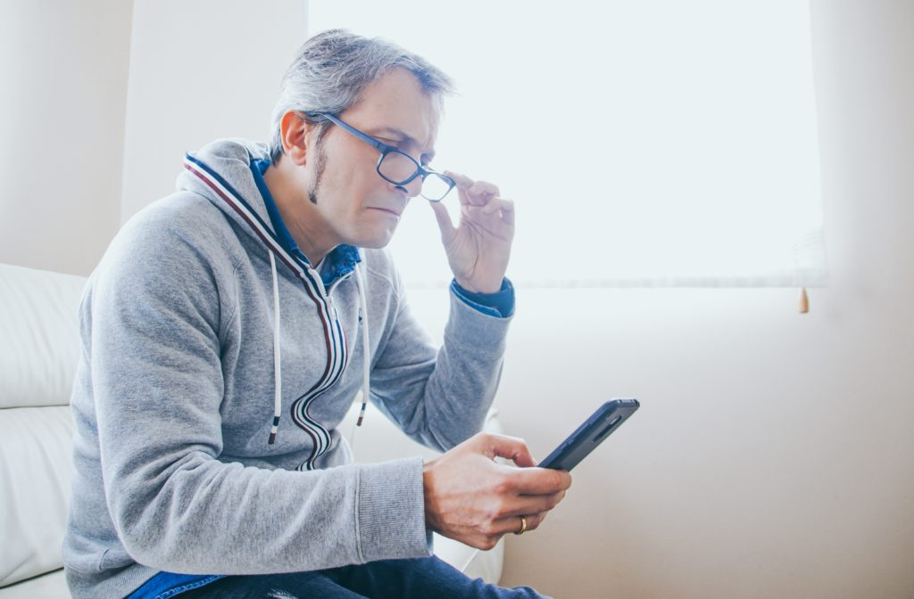 Older man having trouble seeing his phone screen because he is suffering from presbyopia